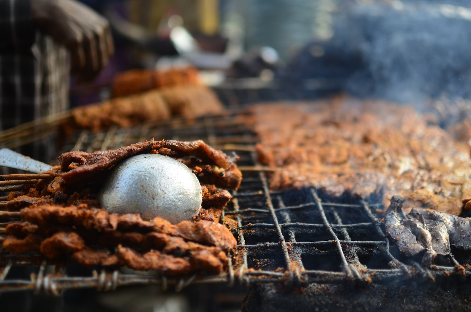 Grilling beef suya, a staple of Nigerian cuisine